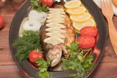 Fische gebacken in der Folie auf einem Behälter Stockfotografie