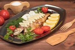 Fische gebacken in der Folie auf einem Behälter Stockfoto