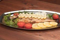 Fische gebacken in der Folie auf einem Behälter Stockbilder