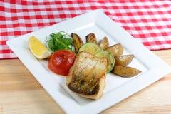Fische gegrillt mit Gemüse auf einem Holztisch Lizenzfreie Stockfotografie
