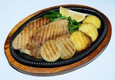 Fische grillten mit Gemüse in einer ovalen Platte auf einem blauen Hintergrund Nahaufnahme Lizenzfreie Stockfotografie