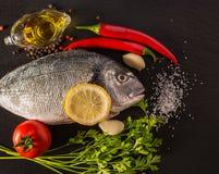Fische mit Gemüse auf einem Steinschiefer Lizenzfreie Stockfotografie