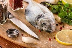 Fische mit Gemüse auf einem Steinschiefer Lizenzfreie Stockfotos