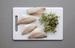 Fische mit Kräutern auf dem hackenden Brett lizenzfreie stockbilder