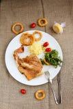 Fische mit Zwiebelringen und rosemarry Stockfotos