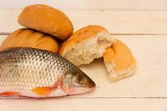 Fische und Brote auf weißem Hintergrund stockbild