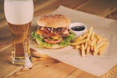 Fische und Chips Burger mit gebratenem Kartoffelstroh, kaltes Bier des frischen Salats Stockfotos