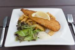 Fische und Chips Served auf quadratischer Platte Stockbild