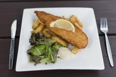 Fische und Chips Served auf quadratischer Plattennahaufnahme Stockfotografie