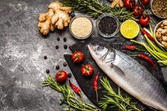 Fische, Wolfsbarsch und Bestandteile für das Kochen: Gemüse, Gewürze Stockfoto