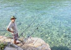 Fischen des älteren Mannes im adriatischen Meer von der Bank Sommer, Sonne, Meer, Angeln Azurblaues klares Meerwasser lizenzfreie stockfotografie