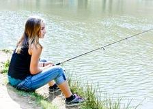 Fischen des jungen jugendlich auf einer Flussquerneigung Stockbilder