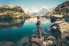 Fischen des jungen Mannes auf See mit Stangenbergen gestalten auf Hintergrund landschaftlich Stockfoto