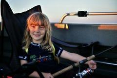 Fischen des kleinen Mädchens, das am Boot mit Stange bei Sonnenuntergang mit der Schleppangel fischen Stockbild