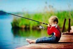 Fischen des kleinen Mädchens vom Dock auf See stockfotografie