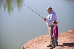 Fischen des kleinen Mädchens zusammen mit Großvater Stockfotos