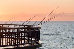 Fischen rodes auf einem Pier bei Sonnenaufgang Stockfotos