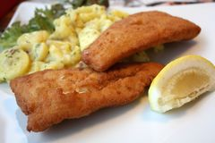 Fischen Sie beim Panieren mit Kartoffelsalat und -zitrone Stockbilder