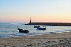 fischen Sie Boote und Leuchtturm in Praia dÂ'Aguda Strand Stockfotografie