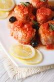 Fischen Sie in der Tomatensauce mit Oliven auf der Plattennahaufnahmevertikale Lizenzfreies Stockbild