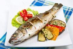 Fischen Sie, der Wolfsbarsch, der mit Zitrone gegrillt werden und gegrilltes Gemüse stockbild
