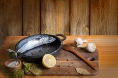 Fischen Sie Makrele, um sich für das Salzen am Tisch vorzubereiten Lizenzfreies Stockbild