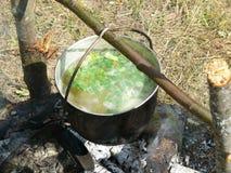 Fischen Sie Suppe eine Melone über einem Lagerfeuer nach einem erfolgreichen Fischen Stockfoto