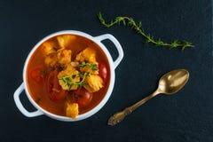 Fischen Sie Suppe mit Kabeljau, Tomate, Zwiebel, Knoblauch und Thymian in der weißen Schüssel auf schwarzem Steinhintergrund, Dra Stockbild