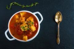 Fischen Sie Suppe mit Kabeljau, Tomate, Zwiebel, Knoblauch und Thymian in der weißen Schüssel auf schwarzem Steinhintergrund, Dra Lizenzfreie Stockbilder