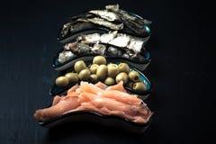 Fischen Sie Zusammenstellung und Oliven auf einer Platte auf einem dunklen Hintergrund mit Lizenzfreies Stockbild