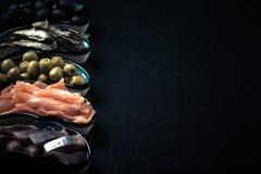 Fischen Sie Zusammenstellung und Oliven auf einer Platte auf einem dunklen Hintergrund mit Lizenzfreie Stockbilder