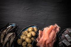 Fischen Sie Zusammenstellung und Oliven auf einer Platte auf einem dunklen Hintergrund mit Lizenzfreies Stockfoto
