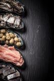 Fischen Sie Zusammenstellung und Oliven auf einer Platte auf einem dunklen Hintergrund mit Stockbilder