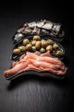 Fischen Sie Zusammenstellung und Oliven auf einer Platte auf einem dunklen Hintergrund mit Stockfotos