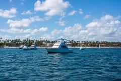 Fischend in Dominica Republic, steht ein weißes Fischerboot auf einem Dock nahe dem Ufer, gegen einen Hintergrund von Palmen und  Lizenzfreies Stockfoto