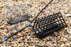 Fischenfuttertröge für das Fangen durch eine Zufuhr auf Steinboden Lizenzfreies Stockfoto