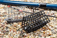 Fischenfuttertröge mit Angelrute aus den steinigen Grund Lizenzfreie Stockbilder