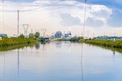 Fischenhütten in der unreinen Lagune mit Industrien Stockfotografie