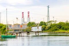 Fischenhütten in der unreinen Lagune mit Industrien Lizenzfreie Stockfotos