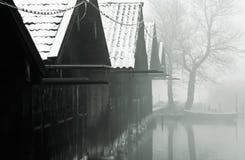 Fischenhütten und nebelhafter See Stockfotografie