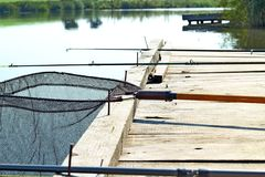 Fischenhintergrund Retro- getontes Bild der Angelausr?stung auf h?lzernem Pier Fischerei der Plattform auf dem See stockfotografie