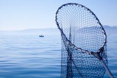 Fischenkescher im blauen Meer Stockfotografie