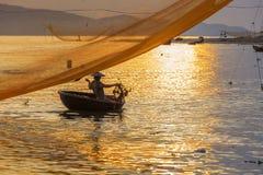 Fischer überprüft seine Netze am frühen Morgen auf Fluss in Hoian, Vietnam stockbilder