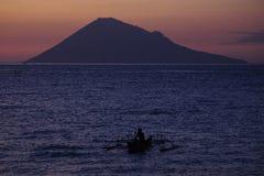 Fischer Alone mit Hintergrund von Insel Manado Tua Stockbild