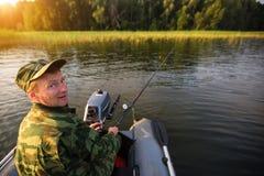 Fischer auf anziehenden Fischen des Gummibootes auf dem Fluss liebhaberei lizenzfreie stockfotografie