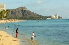 Fischer auf beschäftigtem Strand von Waikiki Stockbilder