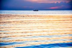 Fischer auf Boot im Dämmerungshimmel Stockfotos