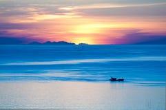 Fischer auf Boot morgens mit Sonnenaufgang lizenzfreie stockbilder