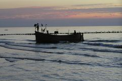 Fischer auf dem Boot, das vom Meer zurückgeht Lizenzfreies Stockbild