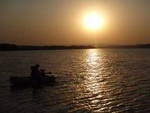 Fischer auf dem Meer bei Sonnenuntergang Lizenzfreie Stockbilder